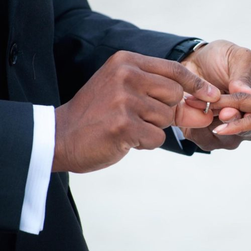 A closeup shot of a groom placing a ring onto his bride's finger.