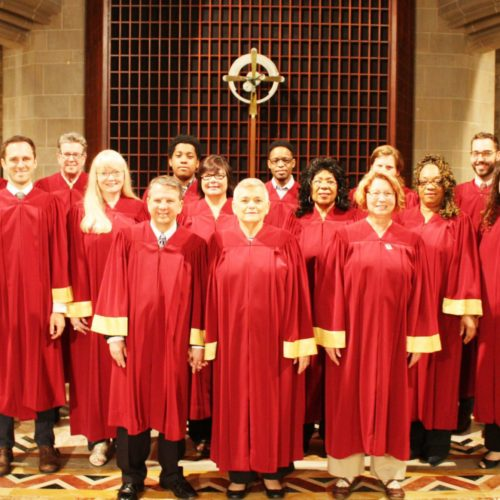 About 13 adults in red and gold robes stand together in the sanctuary.