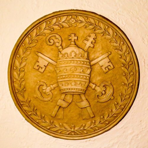 The beautiful medallion in the ceiling of the sacristy shows a bishop's hat over keys and crosiers, surrounded by a leafy wreath.