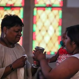 The Eucharistic Minister on the left prepares to receive back the cup from a woman who also holds a little girl in her arm.