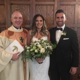 Father J.J. proudly stands next to a newly married couple in their wedding garments. Father holds documents and the bride holds her white flowers.