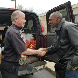 Father J.J. gratefully shakes the hand of a parishioner who has helped to load a van with food for the pantry.