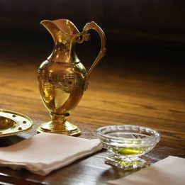 Oil of the sick, a gold cruet, and some linens await their use on a wooden table.