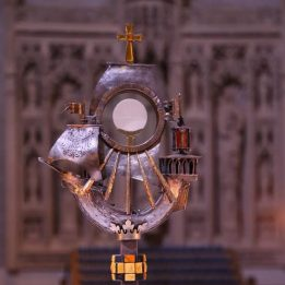 A monstrance in the shape of a ship holds the Most Blessed Sacramnet. In the background are statues of saints.