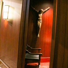 A statue of Jesus Christ hangs on the wooden wall above a chair in the the confessional room, while the light in the hallway welcomes all to draw near.