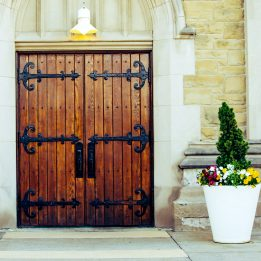 The wooden north doors have lovely ironwork. The stonework surrounding the doors is softened by a welcoming electric light and a pot of purple, white, and yellow pansies surrounding a small evergreen.