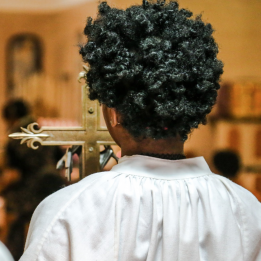 A robed, curly-haired altar server waits to move forward with the processional crucifix.