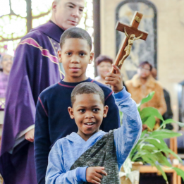 Two boys process down the aisle as Father J.J. watches. The boy in front is smiling and raising a crucifix above his head.