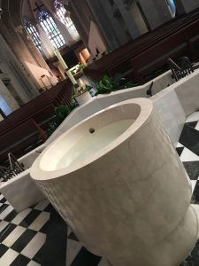 The upper basin of the baptismal font is prominent in a daylit and empty church