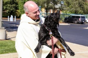 Father J.J. holding his dog.